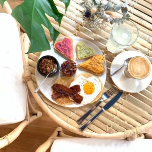 Plate of french homemade pastries with coffee and lemonade on wooden table for brunch at Mademoiselle Simone bordeaux france